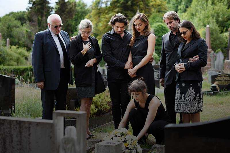 family visiting the gravestone of a family member who died wrongfully